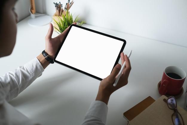 Mężczyzna projektant używa pustego ekranu cyfrowego tabletu z rysikiem na białym biurku
