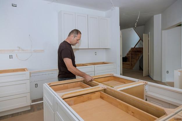 Mężczyzna projektant wnętrz używa taśmy miarę dalej na domowym kuchennym kontuarze