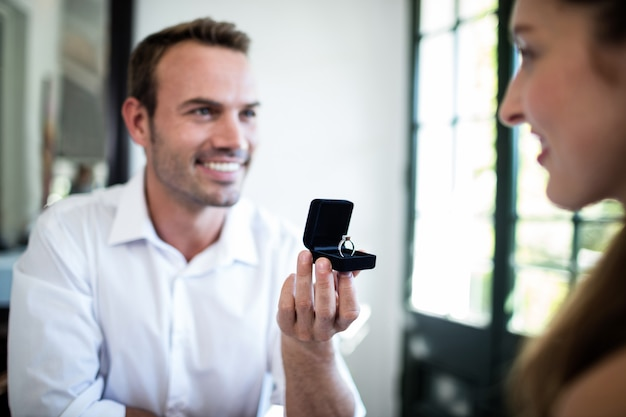 Mężczyzna proponuje kobiecie oferując pierścionek zaręczynowy