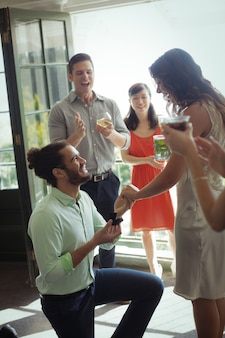 Mężczyzna proponuje kobietę z pierścionkiem zaręczynowym