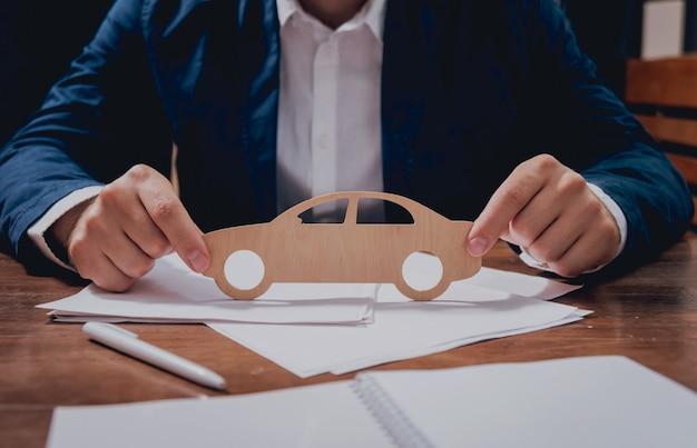 Mężczyzna proponuje podpisanie polisy ubezpieczeniowej samochodu, agent trzyma drewniany model samochodu.