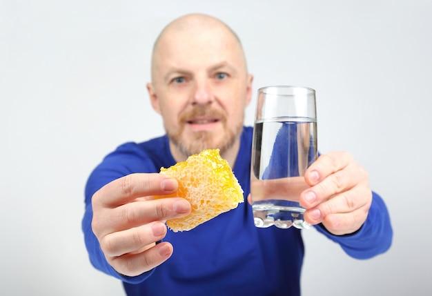 Mężczyzna proponuje zjeść miód z plastra i szklankę wody. zdrowa dieta