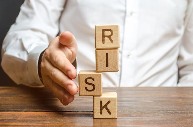 Mężczyzna prostuje segment w niestabilnej wieży z kostkami oznaczonymi ryzyko. zarządzanie ryzykiem