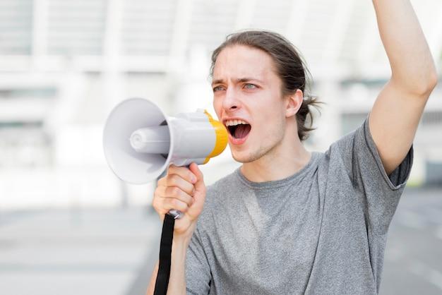 Mężczyzna protestujący krzyczy w megafonie