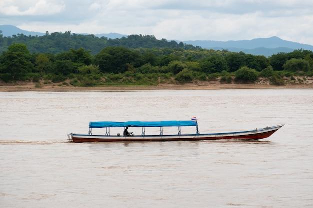 Mężczyzna prowadzący łódkę z długim ogonem na rzece mekhong