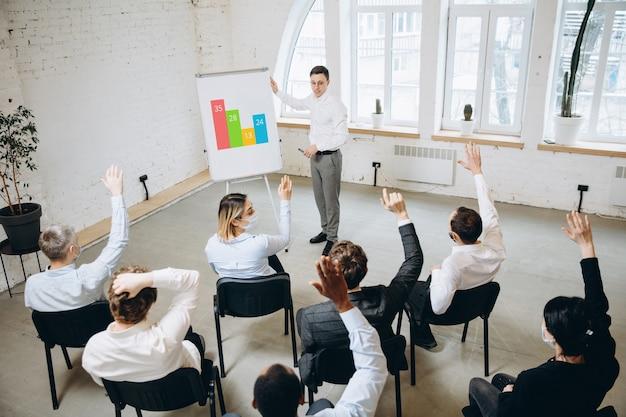 Mężczyzna prowadzący prezentację w sali warsztatów uniwersyteckich. sala widowiskowa lub konferencyjna