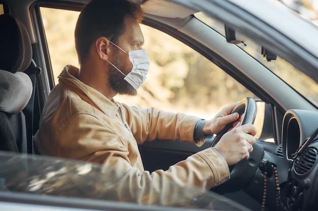 Mężczyzna prowadzący samochód podczas epidemii zakłada maskę medyczną