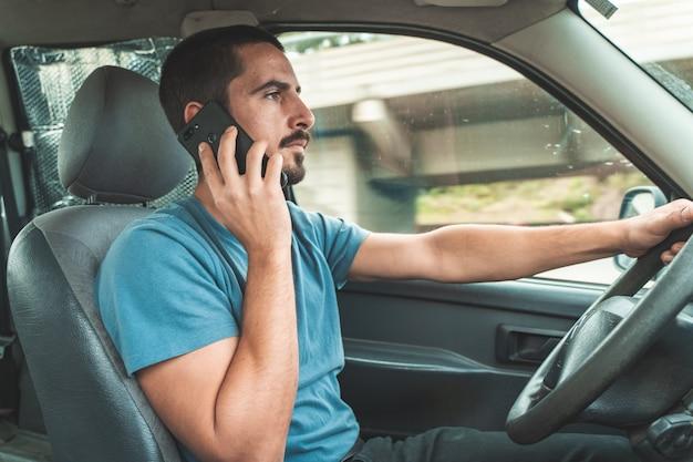 Mężczyzna prowadzący samochód podczas rozmowy przez telefon prowadzenie i wysyłanie sms-ów ze smartfona niebezpieczeństwo rozproszenia uwagi