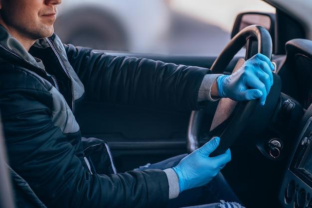 Mężczyzna prowadzący samochód w ochronnej masce medycznej i rękawiczkach. bezpieczna jazda taksówką podczas koronawirusa pandemicznego. chroń kierowcę i pasażerów