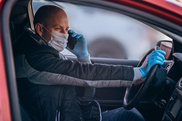 Mężczyzna prowadzący samochód w ochronnej masce medycznej i rękawiczkach rozmawia przez telefon. bezpieczna jazda taksówką podczas koronawirusa pandemicznego. chroń kierowcę