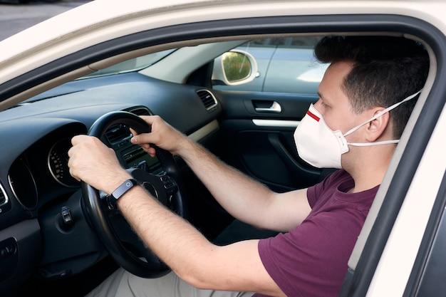 Mężczyzna prowadzący samochód w respiratorze medycznym podczas wybuchu koronawirusa