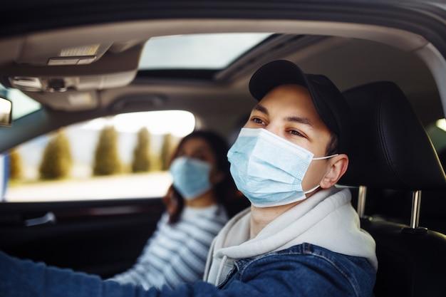 Mężczyzna prowadzący samochód w sterylnej masce medycznej