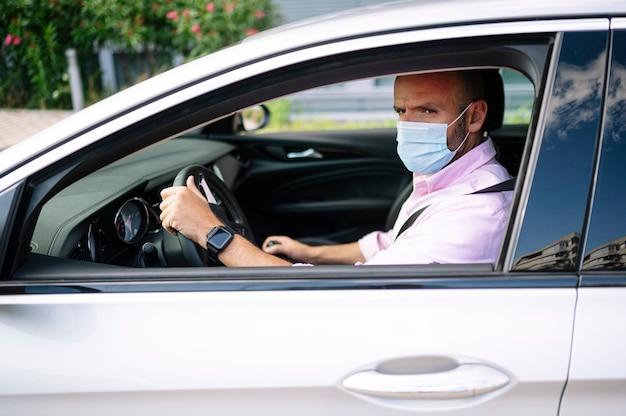 Mężczyzna prowadzący samochód z maską ochronną