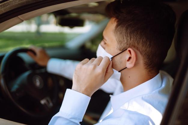 Mężczyzna prowadzący samochód zakłada maskę medyczną podczas epidemii w mieście kwarantanny.