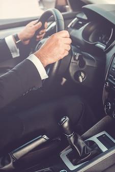 Mężczyzna prowadzący samochód. zbliżenie: mężczyzna w stroju formalnym prowadzący samochód