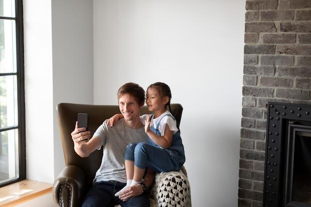 Mężczyzna prowadzi wideorozmowę ze swoją żoną obok córki