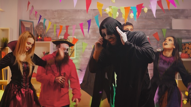 Mężczyzna przebrany za kostucha na imprezie halloween rozmawia przez telefon.