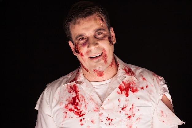 Mężczyzna przebrany za przerażającego zombie na czarnym tle. halloweenowa istota.