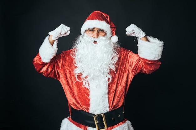 Mężczyzna przebrany za świętego mikołaja wystający biceps obiema rękami na znak siły, na czarnym tle. koncepcja boże narodzenie, święty mikołaj, prezenty, uroczystości.
