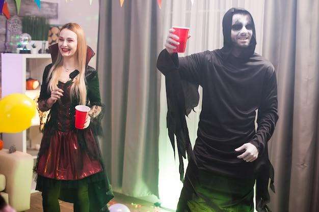 Mężczyzna przebrany za upiornego kostucha na imprezie halloweenowej z przyjaciółmi.