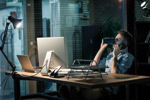 Mężczyzna przeciążony pracą o rozmowę telefoniczną