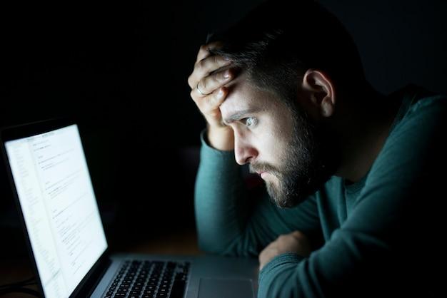 Mężczyzna przed laptopem czytający i skoncentrowany