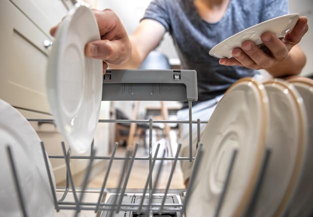 Mężczyzna przed otwartą zmywarką wyjmuje czyste naczynia po umyciu.