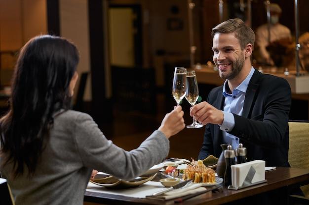 Mężczyzna przedsiębiorca w garniturze czuje się wesoły, stukając się kieliszkami alkoholu z atrakcyjną kobietą naprzeciwko niego
