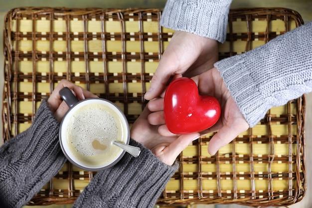 Mężczyzna przedstawia dziewczynie, która pije kawę w prezencie na walentynki