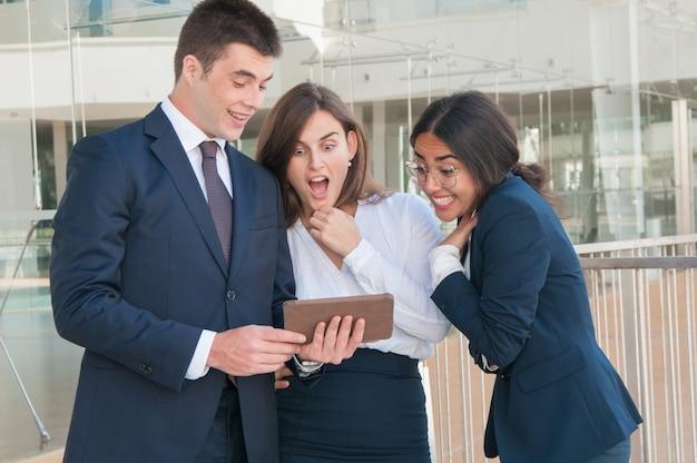 Mężczyzna przedstawia kolegów dane na tablecie, wyglądają na zszokowanych