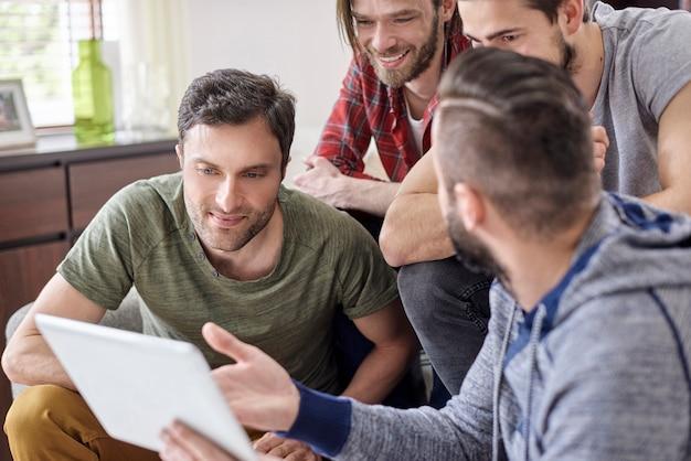 Mężczyzna przedstawia znajomym swój nowy tablet