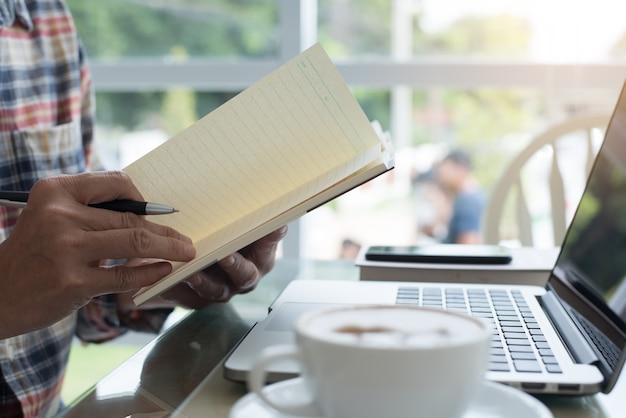 Mężczyzna przeglądający plan pracy i pracujący na komputerze przenośnym w kawiarni