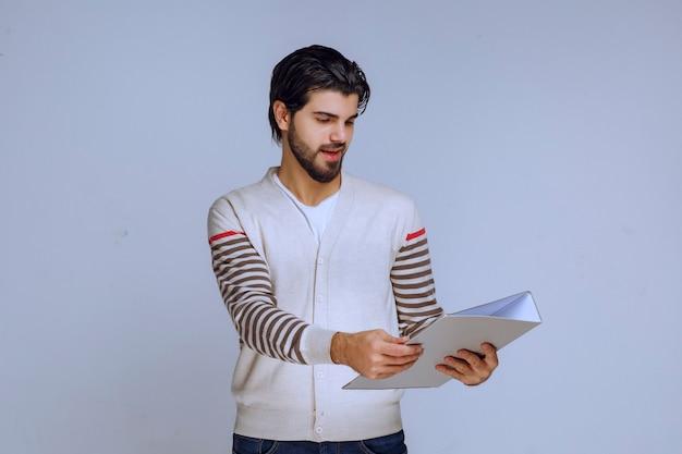 Mężczyzna przekazuje lub otrzymuje folder raportowania.