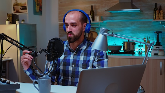 Mężczyzna przemawiający podczas pokazu online do profesjonalnego mikrofonu. kreatywny program online produkcje na żywo gospodarz transmisji internetowej przesyłający treści na żywo, nagrywający komunikację w mediach społecznościowych