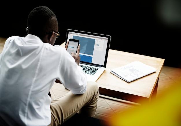 Mężczyzna przesyłający pliki na smartfona i laptopa
