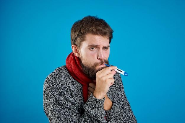Mężczyzna przeziębienie i grypa z termometrem w ręku