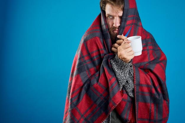 Mężczyzna przeziębienie z grypą na białym tle na niebieskim bakground