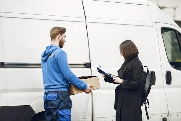 Mężczyzna przy ciężarówce. facet w mundurze dostawczym. człowiek dostawy z paczką na zewnątrz