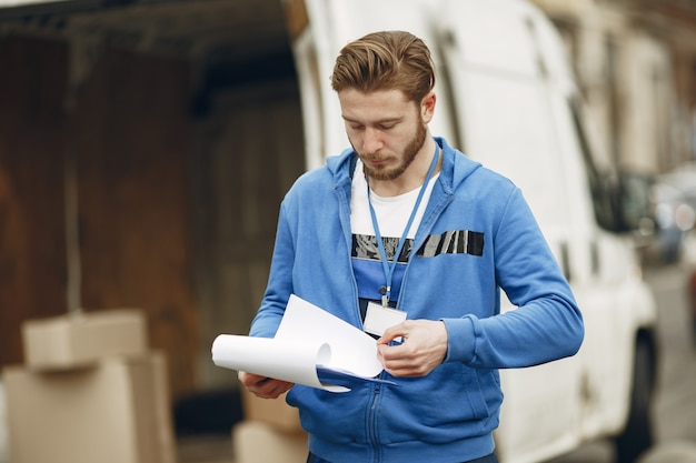 Mężczyzna przy ciężarówce. facet w mundurze dostawczym. człowiek ze schowkiem.