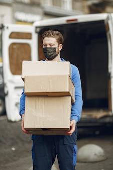 Mężczyzna przy ciężarówce. facet w mundurze dostawczym. mężczyzna w masce medycznej. koncepcja koronawirusa.