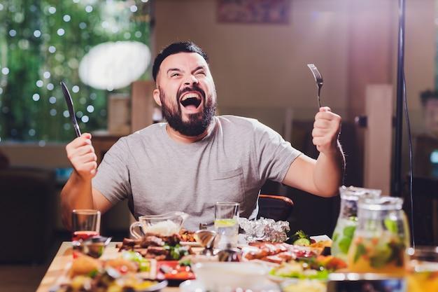 Mężczyzna przy dużym stołem z jedzeniem.