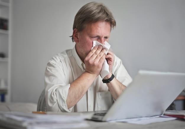 Mężczyzna przy komputerze wydmuchuje nos