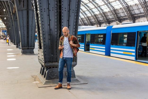 Mężczyzna przy metrem używa smartphone
