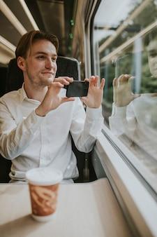 Mężczyzna przy oknie pociągu robi zdjęcie scenerii
