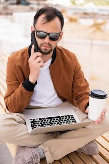 Mężczyzna przy plażą pracuje na laptopie podczas gdy mieć kawę