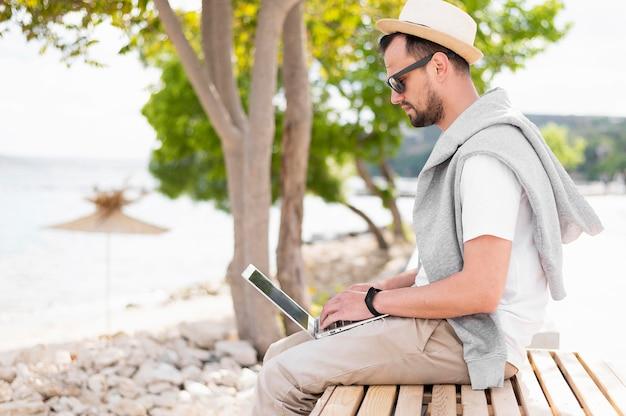 Mężczyzna przy plażą pracuje na laptopie