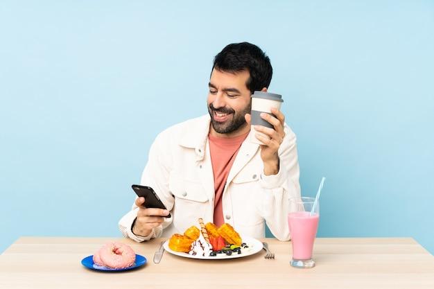Mężczyzna przy stole jedzący gofry śniadaniowe i koktajl mleczny, trzymając kawę na wynos i telefon komórkowy