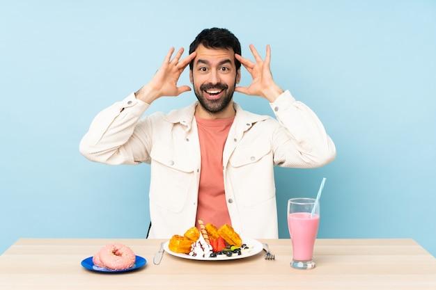 Mężczyzna przy stole o gofry śniadaniowe i mlecznego z wyrazem zaskoczenia