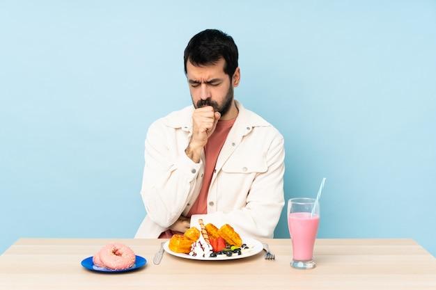 Mężczyzna przy stole z goframi śniadaniowymi i koktajlem mlecznym cierpi na kaszel i źle się czuje