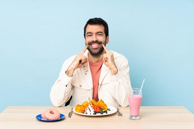 Mężczyzna przy stole z goframi śniadaniowymi i koktajlem mlecznym, uśmiechając się z wyrazem szczęścia i przyjemności